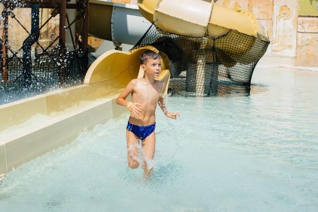 7살짜리 행복한 소년이 워터파크의 미끄럼틀에서 내려옵니다. 행복한 휴가 휴가. 여름 휴가 및 관광.