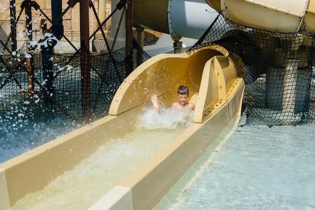 7歳の幸せな男の子がウォーターパークのスライドから降りてきます。幸せな休暇休暇。夏休みと観光。