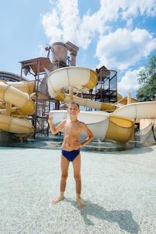 7歳の幸せな男の子が笑顔でウォーターパークのスライドを背景にクラスを示しています。幸せな休暇休暇。夏休みと観光。