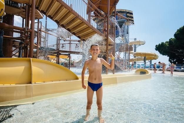 7살 된 행복한 소년이 워터파크에서 슬라이드를 배경으로 미소를 지으며 수업을 보여줍니다. 행복한 휴가 휴가. 여름 휴가 및 관광.