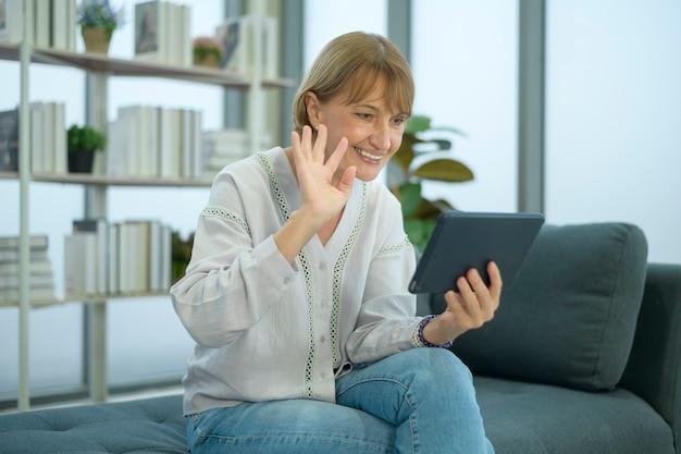 家族や友人への幸せな白人の年配の女性のビデオ通話、家でリラックス、健康な年配の引退した祖父母の笑顔、年上の祖父母の技術の概念