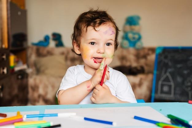 Счастливый жизнерадостный ребенок рисует фломастером в альбоме, используя различные инструменты для рисования.