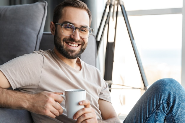 コーヒーを飲みながら家で幸せな陽気な若い男。
