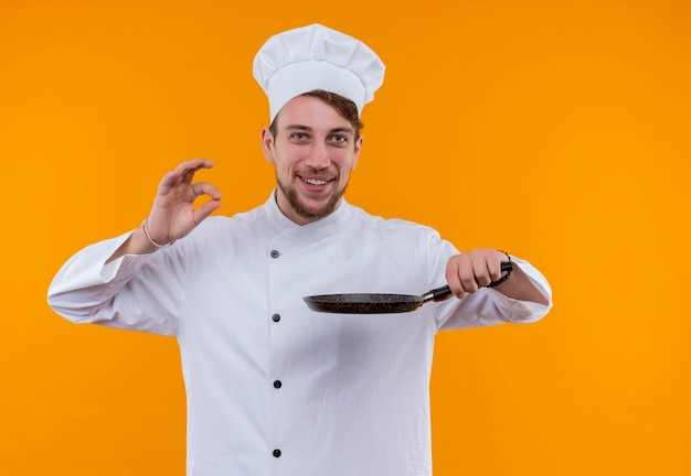 オレンジ色の壁においしいokジェスチャーを表示しながらフライパンを保持している白い制服を着た幸せなシェフの男
