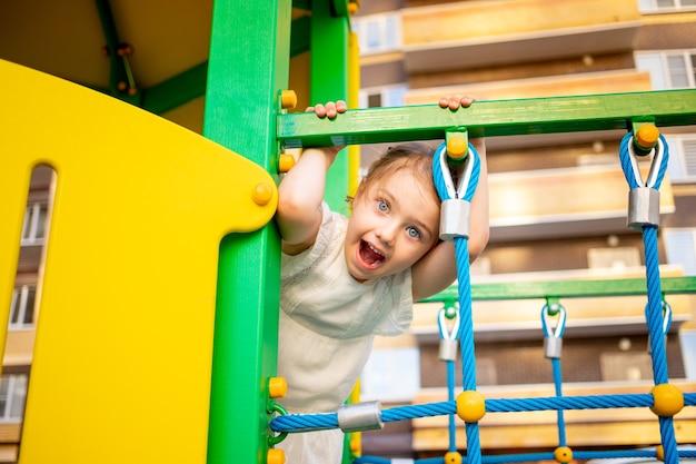 행복한 아이 한 소녀가 여름에 집 근처 놀이터의 어린이 단지에서 마당에서 놀고 놀란다