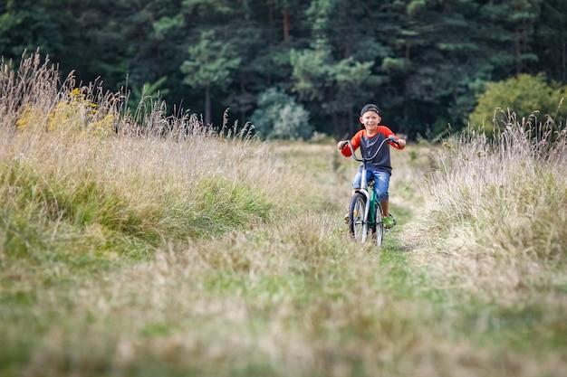自然の中で公園のコンセプトでサイクリング幸せな子供