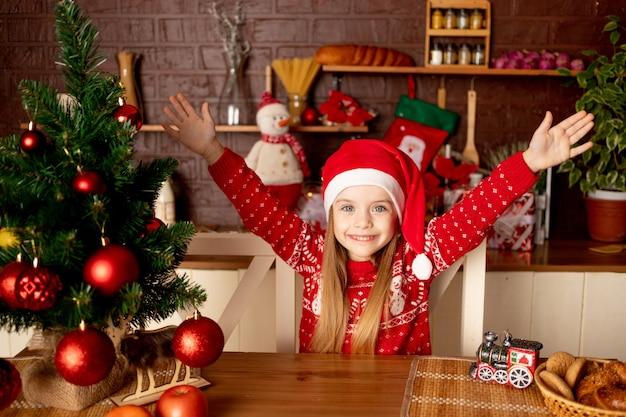 크리스마스 트리의 어두운 부엌에 있는 산타 모자를 쓴 행복한 어린 소녀는 새해와 크리스마스의 개념인 빨간 공을 기뻐하고 미소 짓습니다.