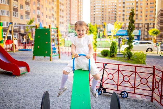 행복한 어린 소녀는 여름에 집 근처 어린이 복합 놀이터에서 마당에서 놀고 웃는다