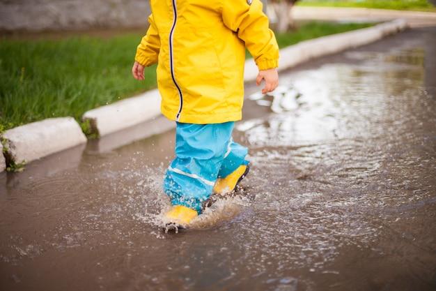 黄色いブーツ、黄色いジャケット、青い明るいズボンを着た幸せな子供が水たまりを歩き、あらゆる方向にスプレーします。春の雨と幸せな子供時代。
