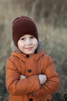 Осенью счастливый ребенок играет в парке и мечтает на свежем воздухе.