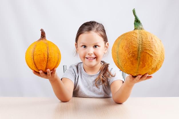 Счастливый ребенок на белой стене держит домашние тыквы из папье-маше на хэллоуин
