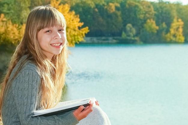公園旅行で自然教育に関する本を読んで幸せな子供