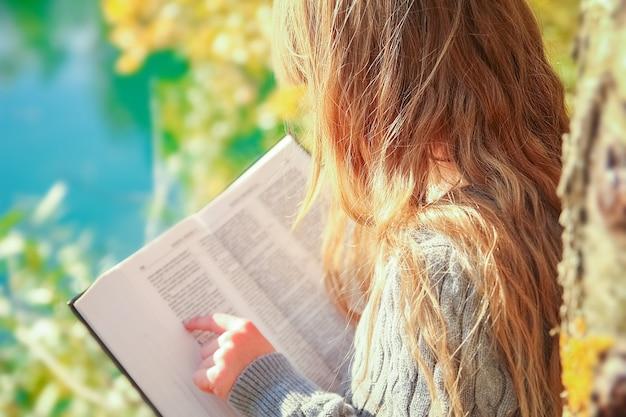 Счастливый ребенок, читающий книгу о природном образовании в путешествии по парку
