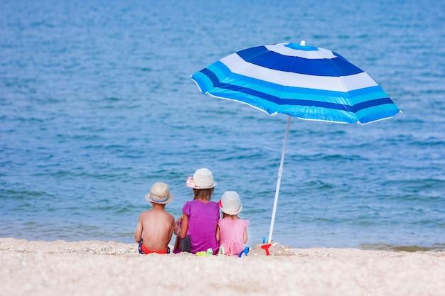 Счастливые дети, играющие на берегу моря с зонтиком