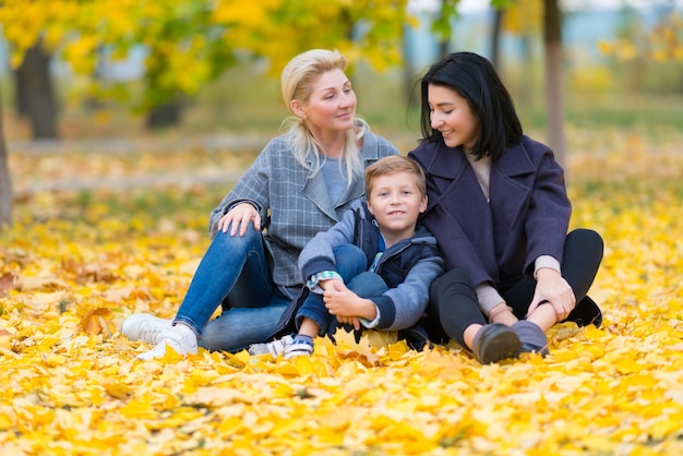 행복한, 콘텐츠 동성 여성 커플과 그들의 아들이 노란색 가을 단풍과 함께 행복한 가족 테마로.