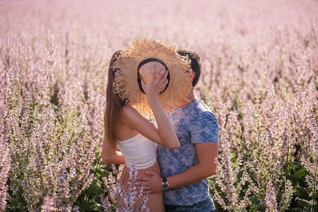 恋に落ちた幸せなカップルが麦わら帽子の後ろに隠れ、日没時に咲くセージ畑の近くでキスをしました。若い男は情熱的に抱きしめ、美しい少女の手を握ります。