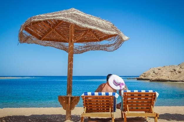 Счастливая пара мужчина и женщина у моря, путешествуя по поверхности в отпуске. парень с девушкой на шезлонге под одеялом ...