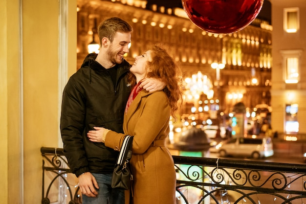 Счастливая пара стоит в объятиях на улице вечером в праздничных огнях