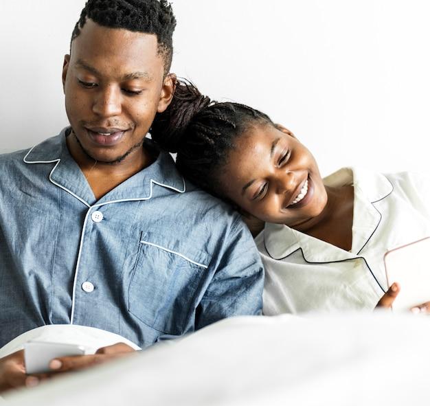 ベッドで携帯電話を使用して幸せなカップル