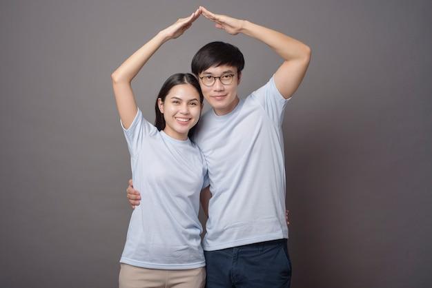 파란색 셔츠를 입고 행복한 커플은 회색에서 팔걸이를 만들고있다