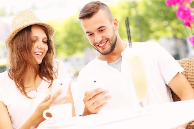Счастливая пара со своими смартфонами в кафе
