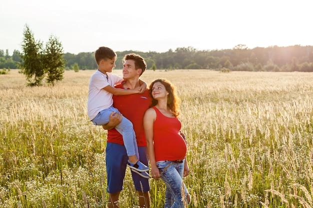 彼らの息子と幸せなカップルは、日没の麦畑の背景にポーズをとっています
