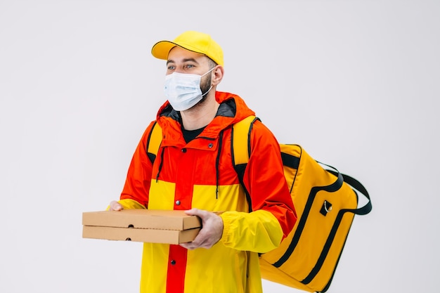 의료용 마스크를 쓴 행복한 택배가 골판지 상자에 피자를 들고 빨간색과 노란색 유니폼을 입고 뒷면에 시원한 가방을 입은 고객에게 선물합니다.