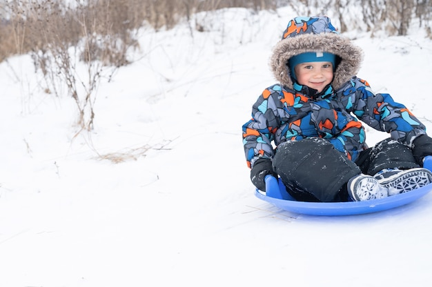 Счастливый милый маленький пятилетний мальчик - это активность и веселье, проводя свои снежные зимние каникулы, катаясь по горке на санях.