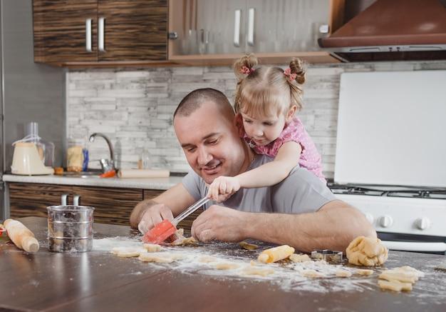 행복한 아빠와 그의 딸이 함께 부엌에서 쿠키를 요리합니다. 공동 요리, 가족 가치