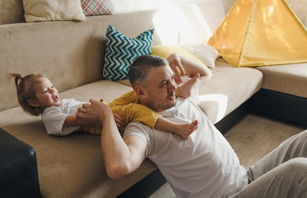 흰색 티셔츠를 입은 행복한 아빠는 딸과 함께 소파에서 놀고 웃고 즐겁게 시간을 보냅니다.