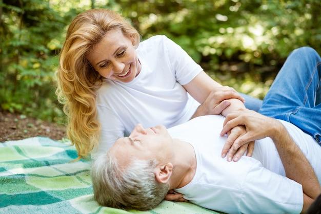 服を着た幸せな老夫婦は、晴れた夏の日に森の中でピクニックにロマンチックな時間を過ごします