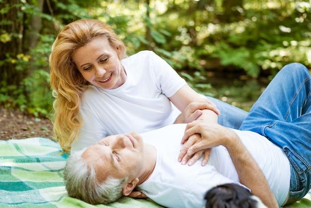 Счастливая пожилая пара в одежде романтично проводит время на пикнике в лесу в солнечный летний день