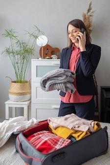 幸せなヨーロッパのミレニアル世代のビジネスウーマンがビジネス用のロードパッキングスーツケースを梱包しています