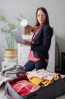 幸せなヨーロッパのミレニアル世代のビジネスウーマンがビジネス用のロードパッキングスーツケースを梱包しています Premium写真