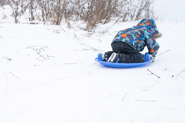 Счастливый безликий пятилетний мальчик весело и весело проводит свои снежные зимние каникулы, катаясь по горке на санях.