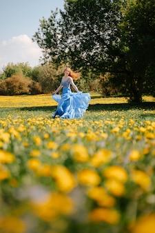 바람이 잘 통하는 파란색 드레스를 입은 행복한 동화 소녀는 노란 민들레 알레르기가 없는 개념으로 꽃이 만발한 공원의 푸른 잔디를 따라 즐겁게 달리고 있습니다.