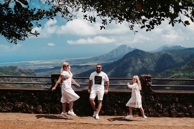 幸せな家族、男、女、娘が山を背景に陽気にジャンプしています