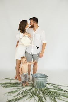 Счастливая семья - отец, мать и их маленький сын возле железной ванны на белом фоне