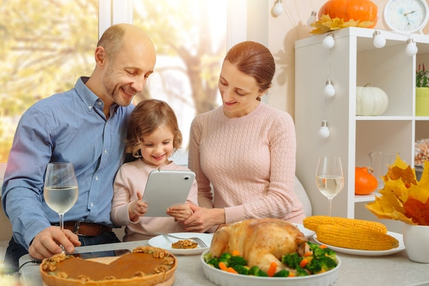 Счастливая семья устраивает ужин в честь благодарения и отправляет своим родителям видеозвонок.