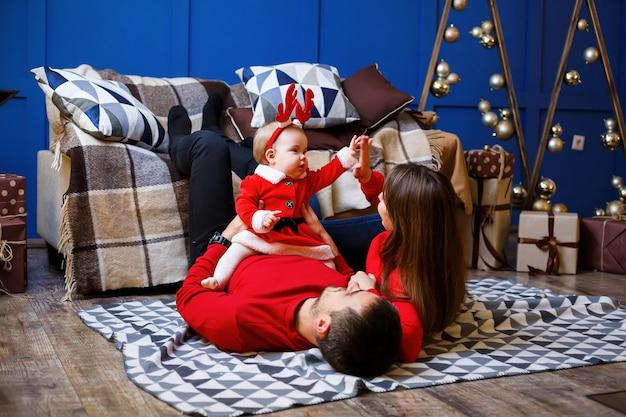 赤いセーターを着た幸せな家族が一緒に床に座っています。クリスマス休暇の雰囲気。サンタの衣装を着た子供。家族関係の概念