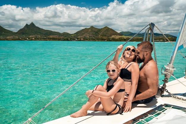 수영복을 입은 행복한 가족이 인도양의 쌍동선에 앉아 있습니다.
