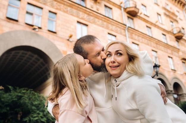 По городу гуляет счастливая семья в белых одеждах. веселая прогулка.