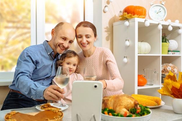 幸せな家族は、ビデオ会議で、感謝祭のディナーを楽しんだり、グラスワインを持ったり、両親に歓声を上げたりしています。
