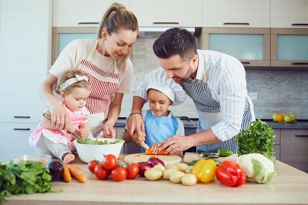 행복한 가족이 부엌에서 야채를 준비하고 있습니다.