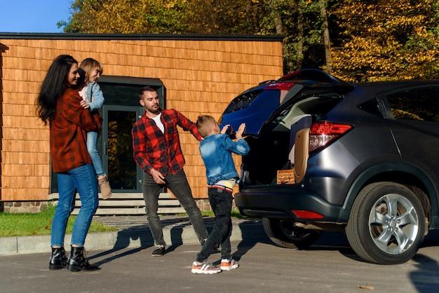 Счастливая семья загружает багаж в багажник автомобиля, собираясь на семейный отдых.