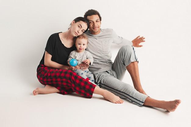 Счастливая семья афро мужчины и кавказской женщины и ребенка на белой студии