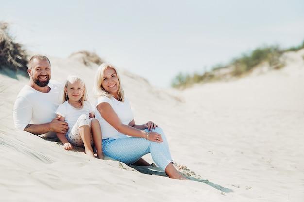 Счастливая семья из трех человек на песчаных дюнах балтийского моря недалеко от города нида. семейный отдых в европе. литва.