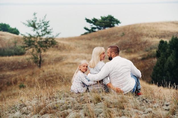 Счастливая семья из трех человек на песчаных дюнах балтийского моря недалеко от города нида. литва.