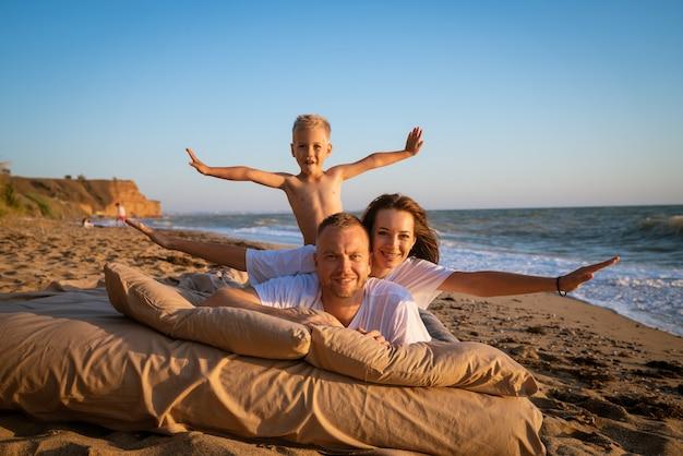 砂浜で休んでいる3人の幸せな家族お母さんは長髪のお父さんとブルネットです...