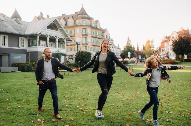 Счастливая семья из трех человек бежит по траве в старом городе австрии. семья гуляет по маленькому городку в австрии. европа. вельден-ам-вертен-зее.
